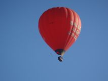 Red hot air balloon floating in the sky. A hot air balloon flying above the Gold Coast, Queensland, Australia on a very clear day Royalty Free Stock Images