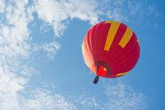 Flying red hot air balloon. The red hot air balloon is flying in the air on cloudy sky Stock Image