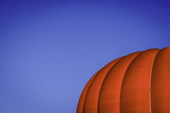 Red Hot Air Balloon rising into frame. Horizontal image showing strong red colour of a balloon against the blue contrast of the sky Royalty Free Stock Images