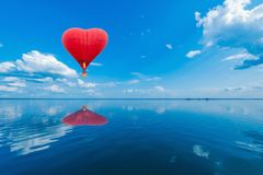 Red hot air balloon in the shape of a heart. Red hot air balloon in the shape of a heart above the lake surface at windless weather time. Present trip on Stock Photo