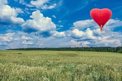 Red hot air balloon in the shape of a heart above the summer meadow. Present trip on Valentine`s Day Royalty Free Stock Photos