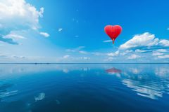 Red hot air balloon in the shape of a heart. Red hot air balloon in the shape of a heart above the lake surface at windless weather time. Present trip on Stock Image