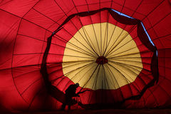 Red hot air balloon silhouette. A crew member is silhouetted by the morning sun while preparing a hot air balloon for launch in the September 2001 Atlantic Stock Photography