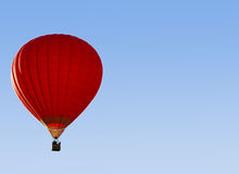 A red hot-air balloon in the sky on a beautiful summer morning. Red hot-air balloon in the sky on a beautiful summer morning Royalty Free Stock Images