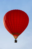 A red hot-air balloon in the sky on a beautiful summer morning. Stock Photo
