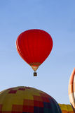 A red hot-air balloon in the sky on a beautiful summer morning. Red hot-air balloon in the sky on a beautiful summer morning Stock Photo