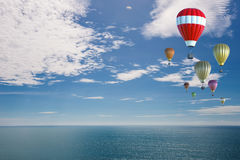 Red hot air balloon with summer background. Red hot air balloon flying in blue sky with blue sea Stock Photos