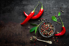 Red hot chili pepeprs and peppercorns on black metal background, top view, copy space for text Stock Photos