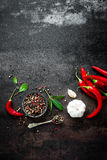 Red hot chili pepeprs and peppercorns on black metal background, top view, copy space for text Stock Images