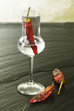Red hot chili pepper grappa glass on ardesia Stock Images