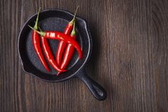 Red hot chili pepper in pan on wood background.  Stock Photos