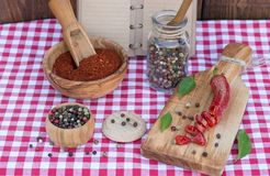 Red hot chili pepper and peppercorn and recipe book on picnic cloth. Crashed Red hot chili pepper and peppercorn and recipe book on picnic cloth Stock Image