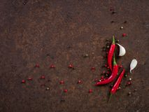 Red hot chili pepper pods and peas, garlic clove on dark rusty m. Etal background, top view, copy space royalty free stock image