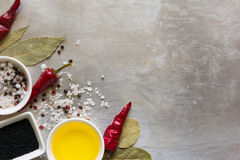 Red hot chili pepper pods peas, salt, oil, black cumin seeds and bay leaves on grey vintage metal culinary background Stock Photography