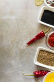Red hot chili pepper pods peas, salt, oil, paprika, cumin seeds and bay leaves on grey vintage metal culinary background Royalty Free Stock Photos