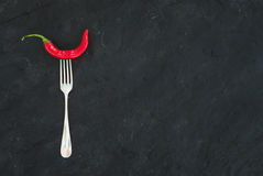 Red hot chili pepper on vintage silver fork over black slate stone background, top view. Red hot chili pepper on vintage silver fork over black slate stone royalty free stock photography