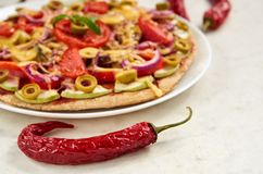 Red hot chili pepper on white surface close up. On blurred background vegetarian pizza with tomatoes, bell pepper, onion Stock Photo