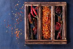 Red hot chili peppers. Assortment of dryed whole and flakes red hot chili peppers in wooden box over dark blue canvas as background Stock Photography