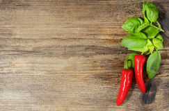 Red hot chili peppers and basil leaves on wood Royalty Free Stock Images
