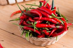 Red hot chili peppers in basket. On wooden table Stock Photo