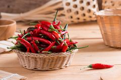 Red hot chili peppers in basket. On wooden table Royalty Free Stock Photography