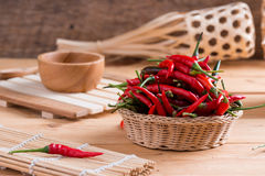 Red hot chili peppers in basket. On wooden table Stock Photography