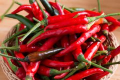 Red hot chili peppers in basket. On wooden table Royalty Free Stock Photos