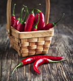 Red Hot Chili Peppers in basket on the wooden background. Stock Photos