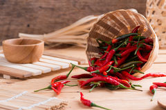 Red hot chili peppers in basket. On wooden table Royalty Free Stock Image