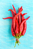 Red hot chili peppers on blue wooden background, top view Royalty Free Stock Images