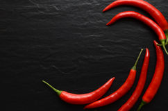 Red hot chili peppers on a dark background. Red hot chili peppers on a dark, stone background Stock Image