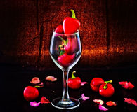 Red hot chili peppers in glass. Red hot chili peppers, a symbol of passion in the shape of heart in glass Stock Image