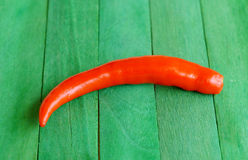 Red hot chili peppers on green wooden Stock Photo