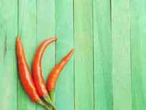 Red hot chili peppers on green wooden Stock Image