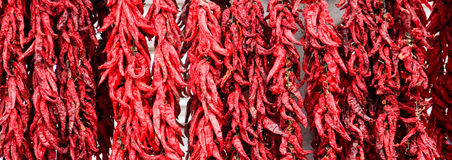 Red hot chili peppers hanging on a ropes on an open market for sale Stock Photo