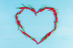 Red hot chili peppers heart on blue wooden rustic table Stock Image