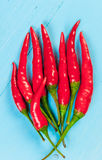 Red hot chili peppers on old blue wooden rustic table Stock Images