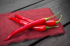 Red hot chili peppers. On old wooden table background Stock Image