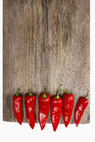 Red hot chili peppers on old wooden table Royalty Free Stock Photos