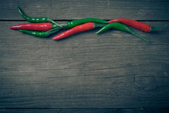 Red hot chili peppers on old wooden table. Tinted Royalty Free Stock Image