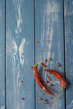 Red Hot Chili Peppers over blue wooden background. Stock Photos