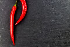 Red hot chili peppers and peppercorns on black background, top v Stock Photos