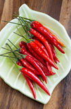 Red hot chili peppers on plate over wooden background Stock Photo