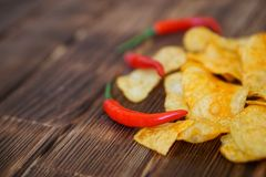 Red hot chili peppers and potato chips lie on a wooden table made of pine boards. Daylight. Close-up. Shallow depth of field stock image