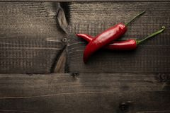 Red Hot Chili Peppers on Rustic Wooden Background. Fresh Red Hot Chili Peppers on Dark Rustic Wooden Background Royalty Free Stock Photography
