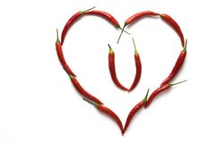 Red hot chili peppers in the shape of a heart symbolizing love isolated on white background. Royalty Free Stock Image