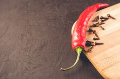 Red hot chili peppers and spices on a empty cutting board/Red hot chili peppers and spices on a empty cutting board on a dark stock photography