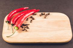 Red hot chili peppers and spices/ Red hot chili peppers and spices on a empty cutting board. Copy space royalty free stock photos