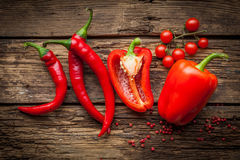 Red hot chili peppers, sweet pepper on wooden table. Red hot chili peppers, sweet pepper on old wooden table Royalty Free Stock Images