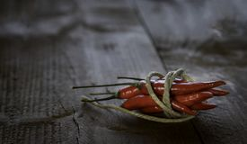 Red hot chili peppers tied by a string. On a rustic wooden table. Copy space stock photography